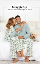 Couple sitting on the couch wearing matching Balsam & Pine Pajamas with the following copy: Snuggle Up - Perfect for a Date Night at Home image number 1