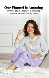 Model sitting on bed wearing Purple Purrfect Flannel Pajamas with the following copy: Timeless pajama features a jersey top and soft, brushed flannel pants image number 3