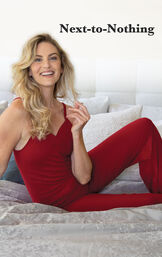 Model sitting on bed wearing Naturally Nude Cami Pajamas - Red with the following copy: Next-to-Nothing image number 2