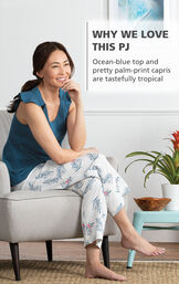 Model wearing Margaritaville Easy Island Capris Pajamas - Blue/White sitting on chair, with the following copy: Ocean-blue top and pretty palm-print capris are tastefully tropical image number 2