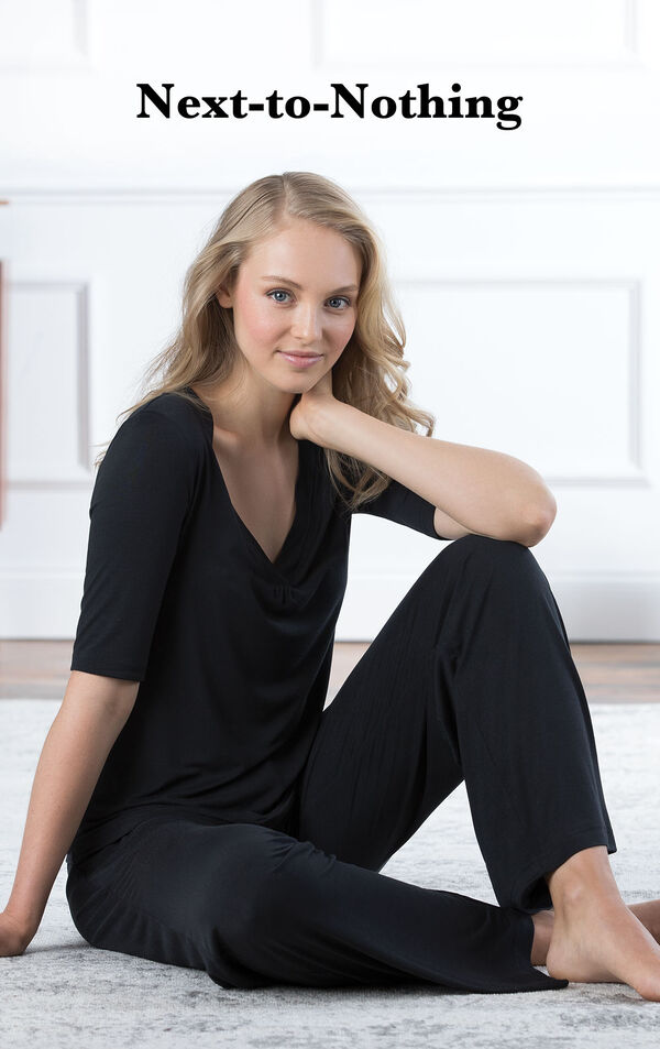 Model sitting down wearing Black Nudies Pajamas with the following copy: Next-to-Nothing. image number 2