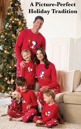 Parents and children and dog wearing Red Snoopy and Woodstock Matching Family Pajamas. Headline: A Picture-Perfect Holiday Tradition. image number 1