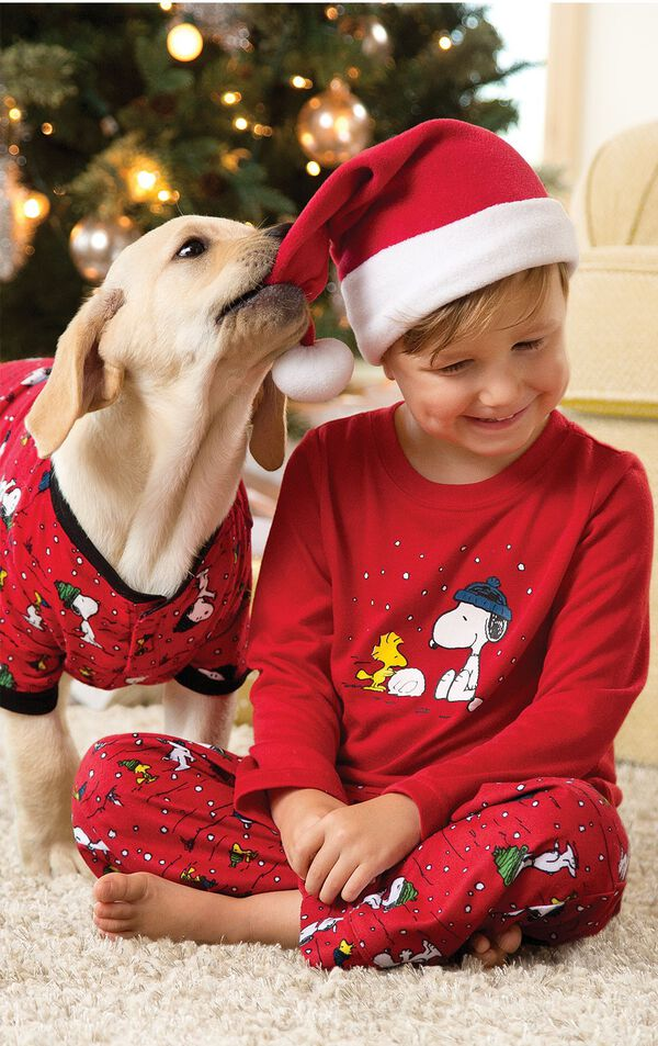 Boy sitting cross legged by Christmas Tree wearing Red Snoopy and Woodstock Toddler Pajamas and a Santa Hat, with his dog whom is wearing matching Snoopy Pajamas image number 1