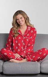 Model sitting cross-legged on couch wearing Red St. Nick Boyfriend Pajamas image number 3