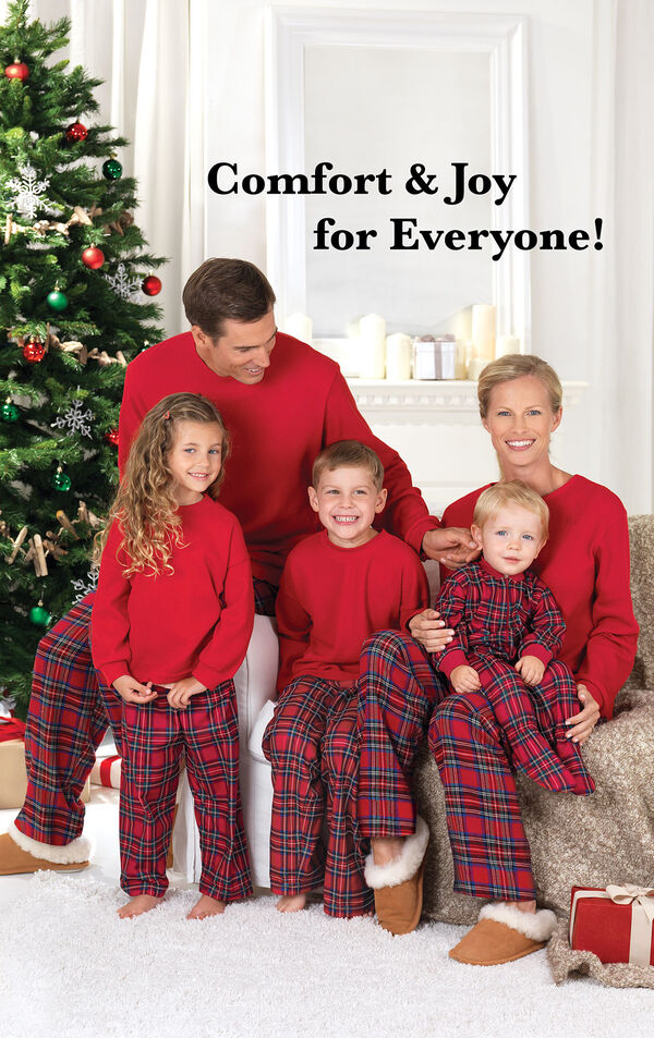 Parents and children sitting by Christmas tree wearing Red Stewart Plaid Thermal-Top Pajamas. Headline: Comfy and Joy for Everyone! image number 1