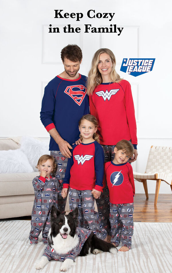 Family standing by couch wearing Justice League Matching Family Pajamas with the following copy: Keep Cozy in the Family image number 1