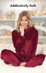 "Model sitting cross-legged on a couch wearing Tempting Touch PJs - Garnet with the following copy: Addictively Soft"" image number 2"