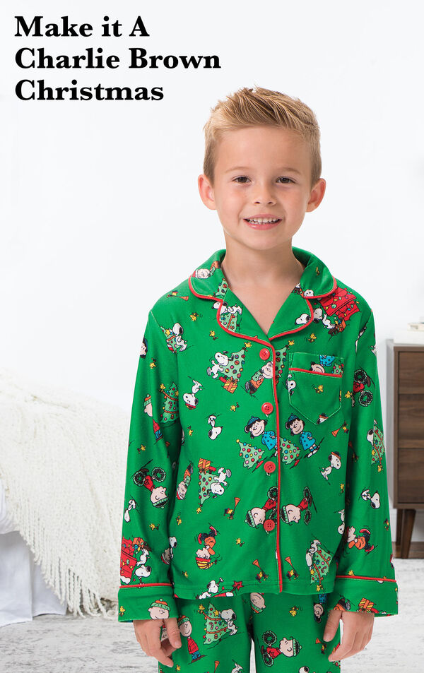 Boy wearing Charlie Brown Christmas Boys Pajamas by bed with the following copy: Make it a Charlie Brown Christmas. image number 1