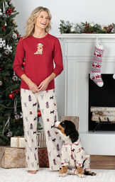 Woman standing in front of fireplace wearing Red and White Holiday Dog Print PJs, playing with dog who is wearing matching pajamas image number 1