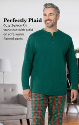 Model wearing Christmas Tree Plaid Men's Pajamas by couch with the following copy: Cozy 2-piece PJs stand out with plaid on soft, warm flannel pants image number 2