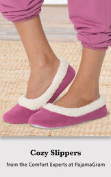 Model wearing Raspberry World's Softest Slippers standing on a rug with the following copy: Cozy Slippers from the Comfort Experts at PajamaGram image number 2