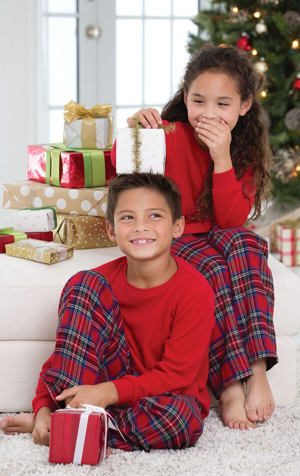 Brother and sister sitting in front of Christmas Tree with presents, wearing matching Classic Red Stewart Plaid Thermal-Top Pajamas image number 2