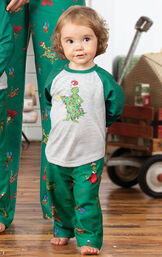 Model wearing Dr. Seuss The Grinch Toddler Pajamas standing in front of a toy wagon image number 2