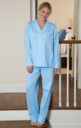 Model standing on stairs wearing light blue button-up pajamas with white polka dots image number 1
