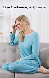 Model sitting on a couch wearing Teal World's Softest Jogger Pajamas with the following copy: Like Cashmere, only better. image number 2