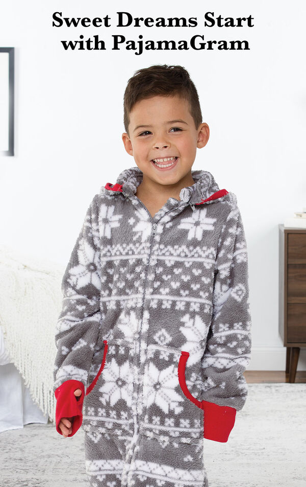 Boy wearing Nordic Fleece Hoodie-Footie by bed with the following copy: Sweet Dreams Start with PajamaGram. image number 1