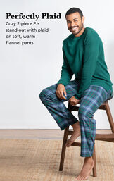 Model wearing Heritage Plaid Thermal-Top Men's Pajamas sitting on a chair with the following copy: Perfectly Plaid. 2-piece thermal PJs stand out with plaid on soft, warm flannel pants image number 2