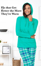 Model standing in kitchen wearing Wintergreen Plaid Hooded Women's Pajamas with the following copy: PJs that get better the more they're worn image number 2