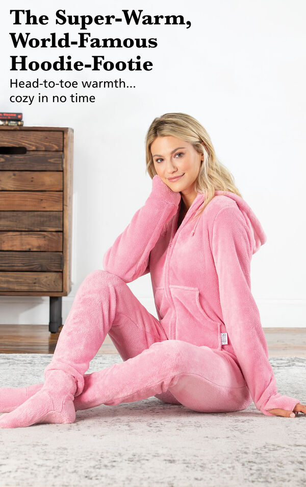 Model sitting on a bed wearing a Pink Hoodie-Footie with the following copy: The Super-Warm, World-Famous Hoodie-Footie. Head-to-toe warmth, cozy in no time. image number 2