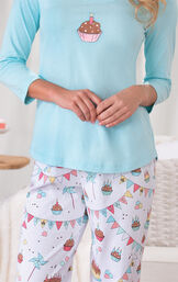 Close-up of Allover Cupcake Print on the white pants, and Cupcake with Candle Graphic on the light blue top image number 3