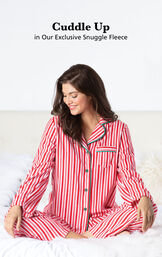 Model sitting cross legged wearing Red and White Stripe Candy Cane Fleece Women's Pajamas with the following copy: Cuddle Up in our Exclusive Snuggle Fleece image number 1