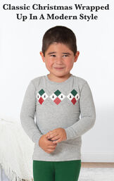 Model standing by bed wearing Green and Gray Holiday Argyle Toddler Pajamas with the following copy: Classic Christmas wrapped up in a modern style image number 2