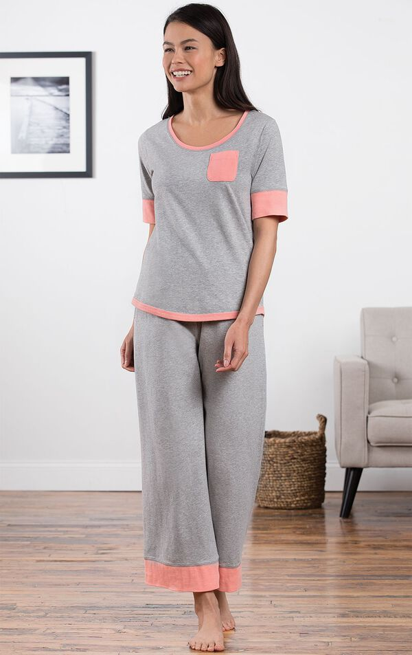 Model standing in living room wearing Gray Cozy Capri Pajama Set with Coral trim and chest pocket image number 1