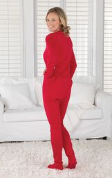 Model wearing Red Dropseat Women's Pajamas by couch, turned away but looking back at the camera image number 1
