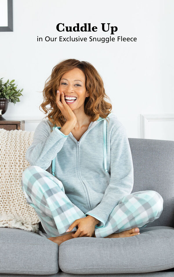 Model sitting on couch wearing Aqua and Gray Snuggle Fleece Hoodie Pajamas with the following copy: Cuddle Up in our Exclusive Snuggle Fleece image number 3