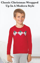 Boy standing by bed wearing Gray and Red Holiday Argyle Boy's Pajamas with the following copy: Classic Christmas wrapped up in a modern style image number 2