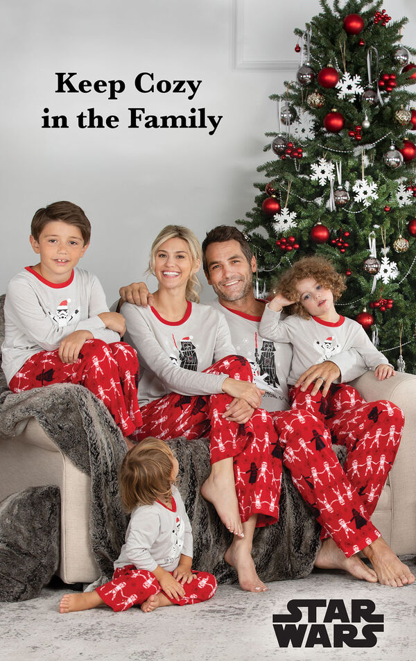 Family sitting by Christmas Tree wearing Red Star Wars Matching Family Pajamas with the following copy: keep Cozy in the Family image number 1