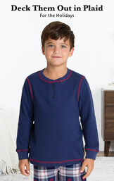 Boy wearing Snowfall Plaid Boys Pajamas by bed with the following copy: Deck Them Out in Plaid for the Holidays. image number 1