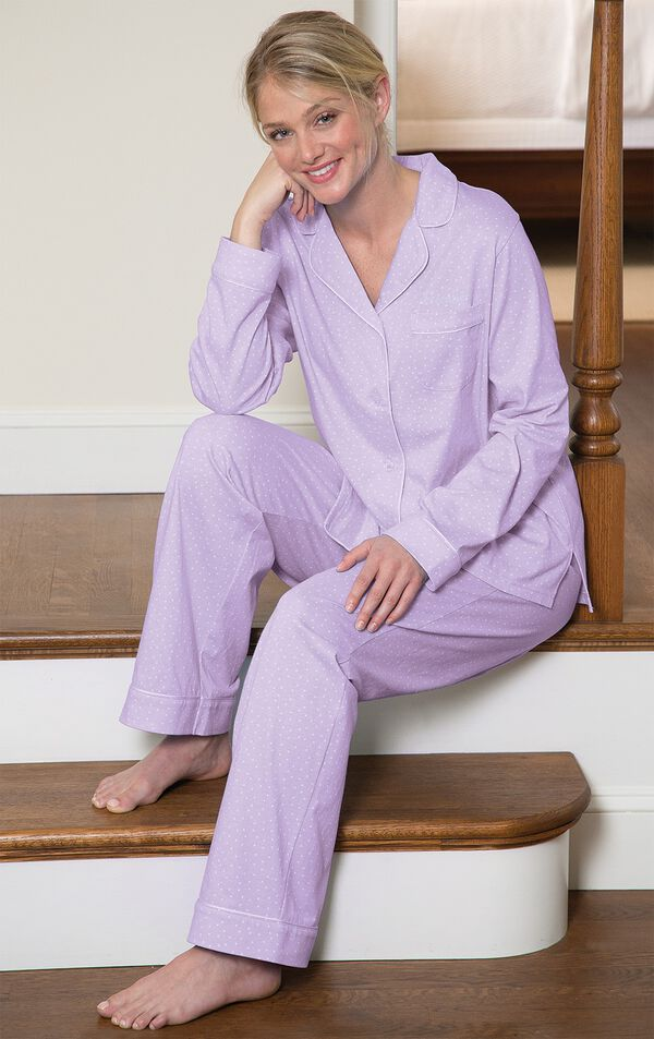 Model sitting on stairs wearing light purple button-up pajamas with white polka dots image number 1