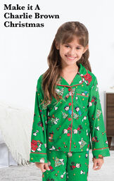 Girl wearing Charlie Brown Christmas Pajamas by bed with the following copy: Make it a Charlie Brown Christmas. image number 1