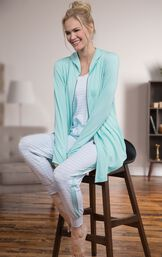 Model sitting on a stool wearing the full Three-Piece Cute Pajama Set  - jogger pants, tank top and Mint zip-up hoodie image number 5