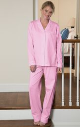 Model standing on stairs wearing pink button-up pajamas with white polka dots image number 1