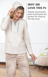 Model standing by couch wearing Margaritaville Cool Nights Hoodie Pajamas - Sand with the following copy: Hoodie top and pretty blue striped pants are perfect for relaxing the day away image number 3
