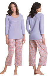 Model wearing Solid Lavender 3/4-sleeve top with Lavender floral print capris pajamas, facing away from the camera and then facing to the side image number 1