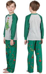 Model wearing Dr. Seuss' The Grinch Boys Pajamas, facing away from the camera and then to the side image number 1