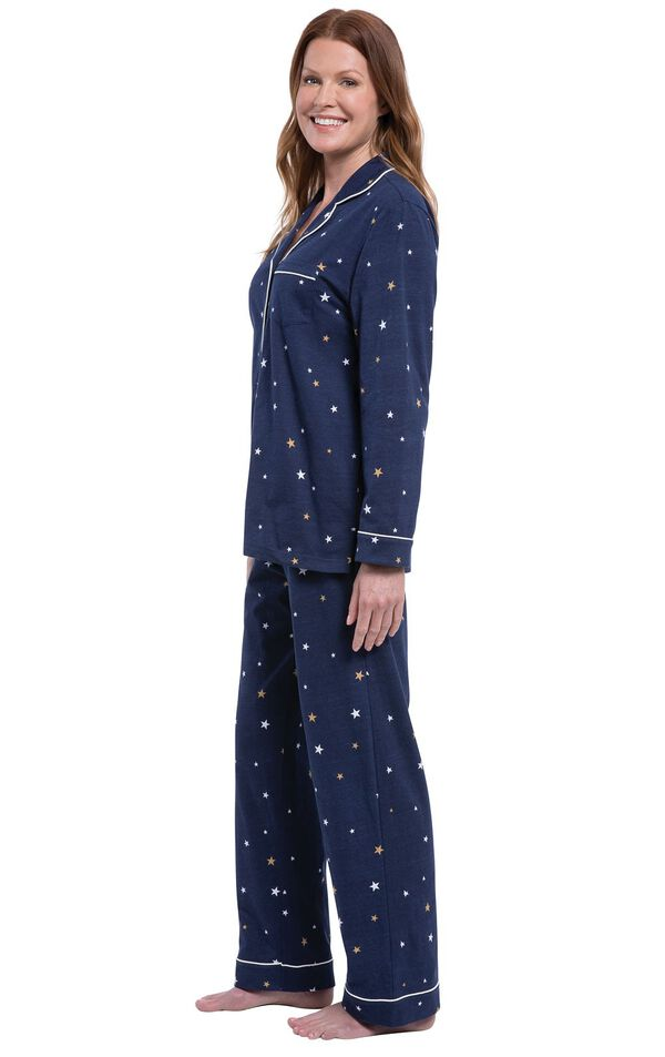 Model facing the side wearing Starry Night Boyfriend Pajamas; Navy blue button up pajamas with yellow and white star allover print image number 2