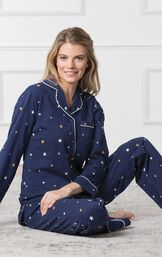 Model sitting down wearing Starry Night Boyfriend Pajamas; Navy blue button up pajamas with yellow and white star allover print image number 3
