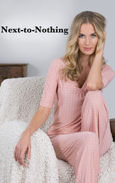 Model wearing Nudies Pajamas sitting on a chair with the following copy: Next-to-Nothing. image number 2