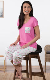 Model sitting in a chair wearing Flamingo Stripe Short-Sleeve Capri Pajamas image number 2