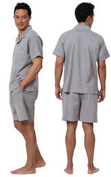 Model wearing Gray Stripe Short Sleeve Button-Front Short Set for Men, facing away from the camera and then facing towards the side image number 1