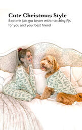 Woman and Dog wearing matching pajamas in bed with the following copy: Cute Christmas Style - bedtime just got better with matching PJs for you and your best friend image number 1