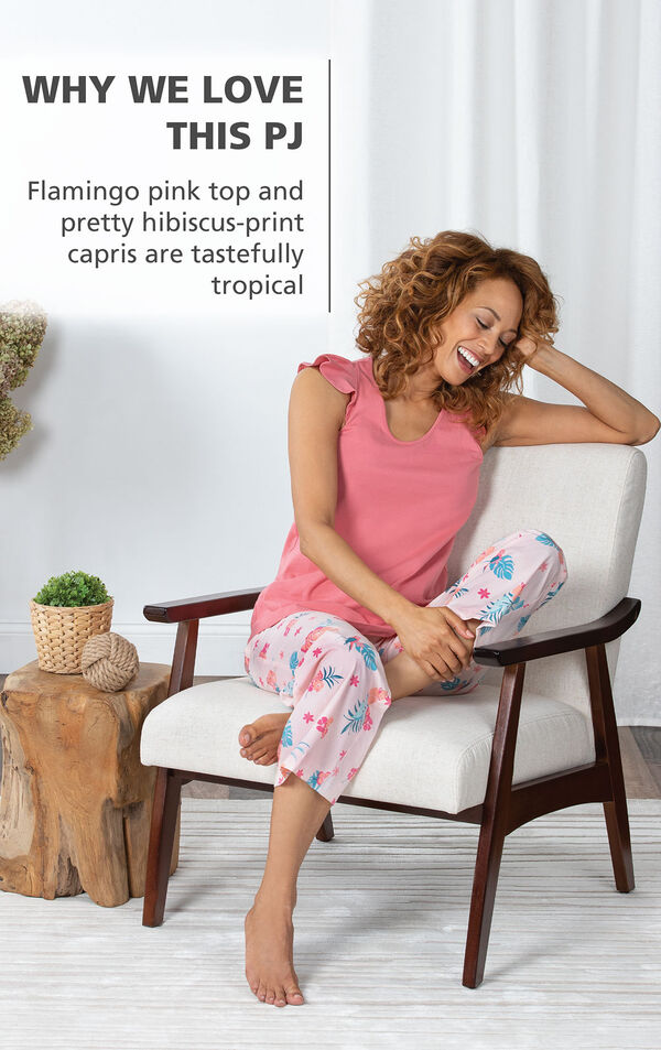 Model wearing Margaritaville Easy Island Capris Pajamas - Pink sitting on chair, with the following copy: Flamingo pink top and pretty hibiscus-print capris are tastefully tropical image number 2