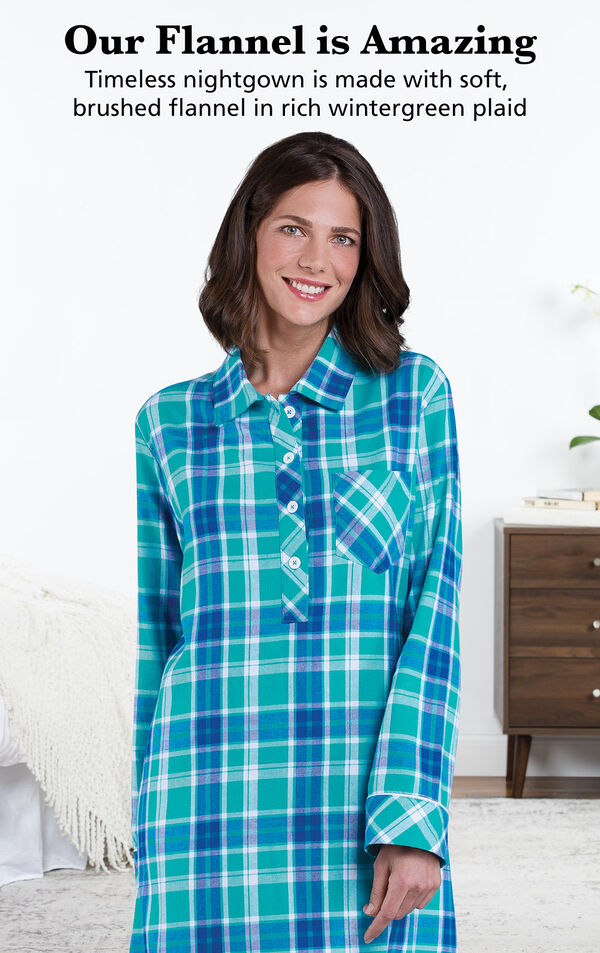 Model wearing Wintergreen Plaid Flannel Nighty by bed with the following copy: Our Flannel is Amazing. Timeless nightgown is made with soft, brushed flannel in rich wintergreen plaid image number 2