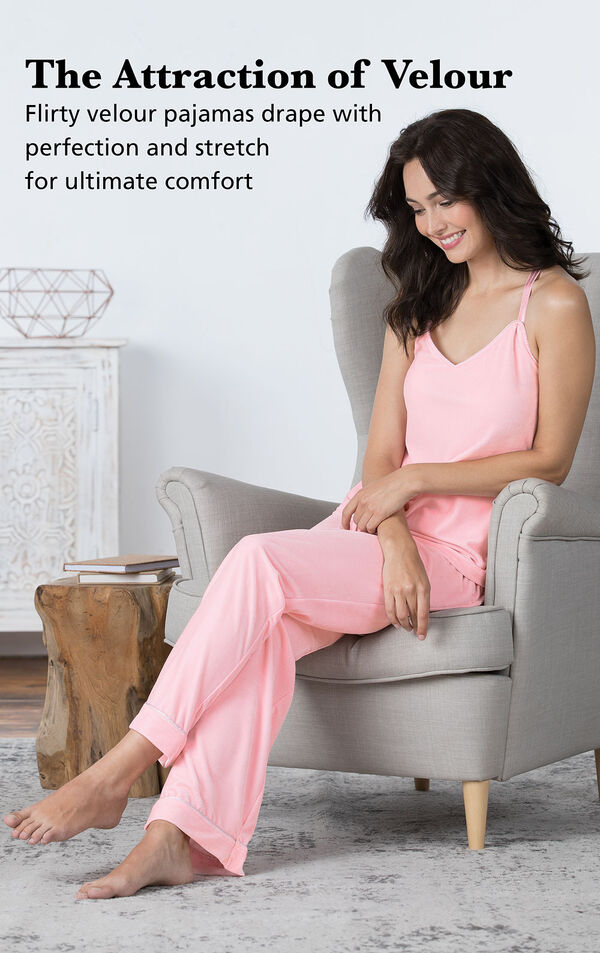 Model sitting in chair wearing Velour Cami Pajamas - Pink with the following copy: The Attraction of Velour. Flirty velour pajamas drape with perfection and stretch for ultimate comfort. image number 2