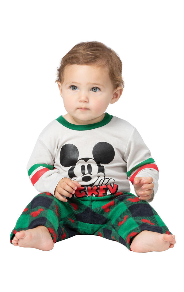 Model sitting on ground wearing Red and Green Mickey Mouse Holiday Pajamas for Infants image number 0