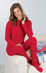 Model sitting on couch with Christmas presents wearing Red Dropseat Women's Pajamas image number 3